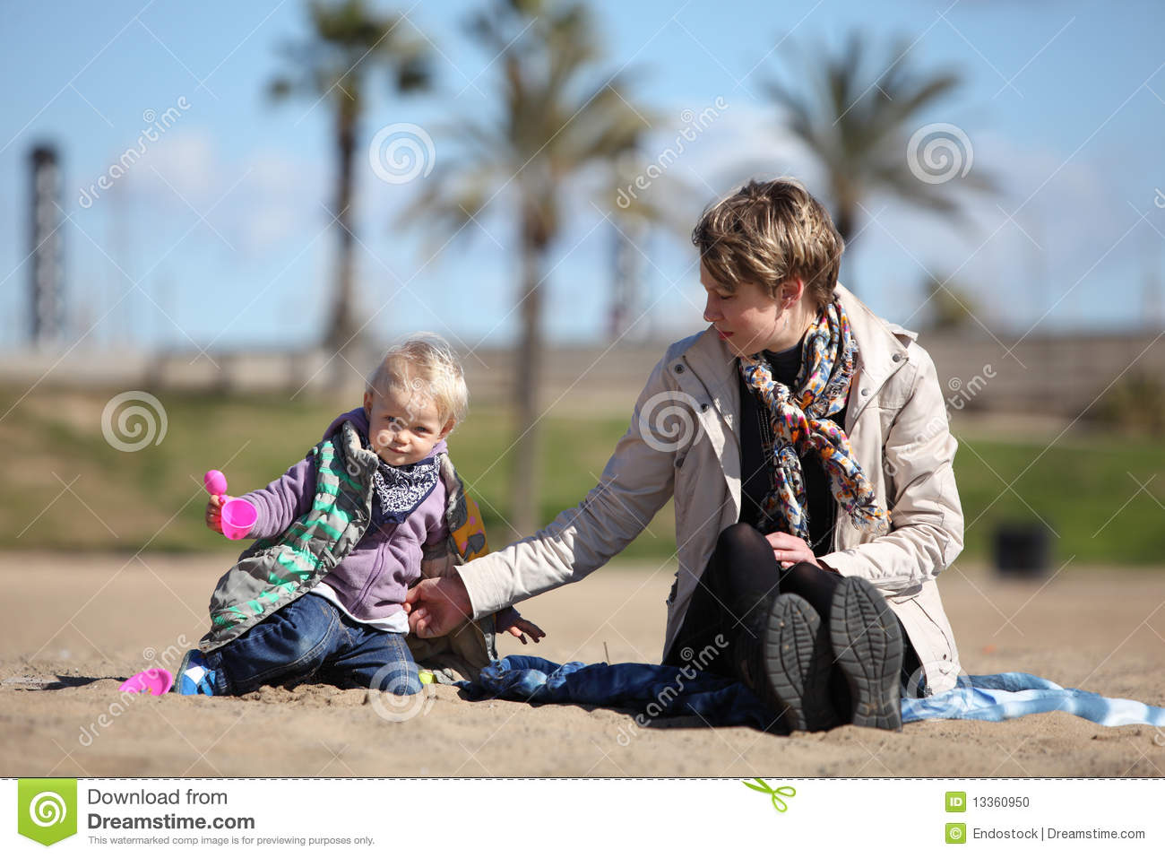 Little daughter and mother playing on the sand