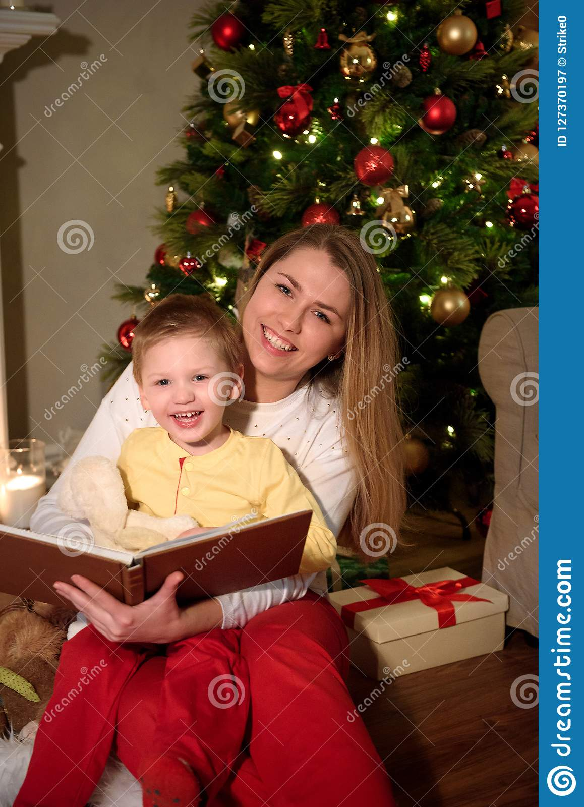Boy and his mom reading a book together laughing