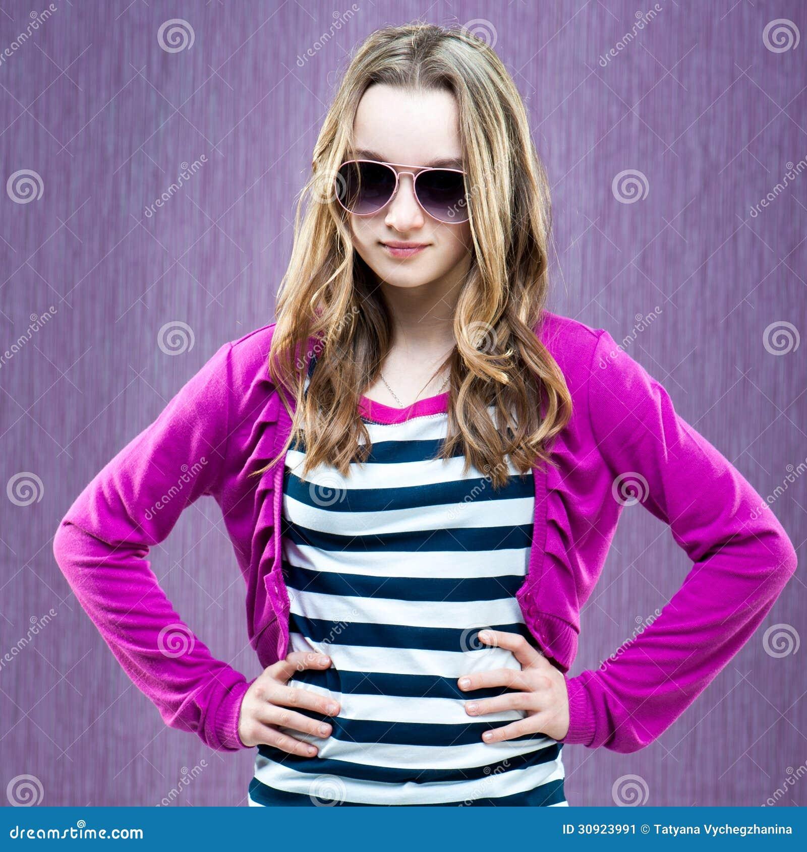 Beautiful little fashion model in sunglasses on a purple background