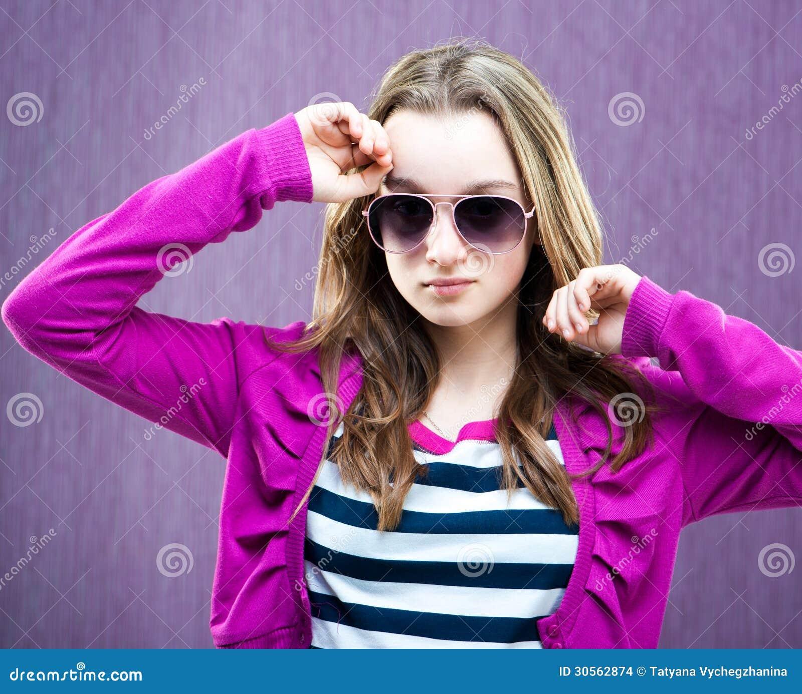 Portrait of a beautiful little fashion model in sunglasses on purple