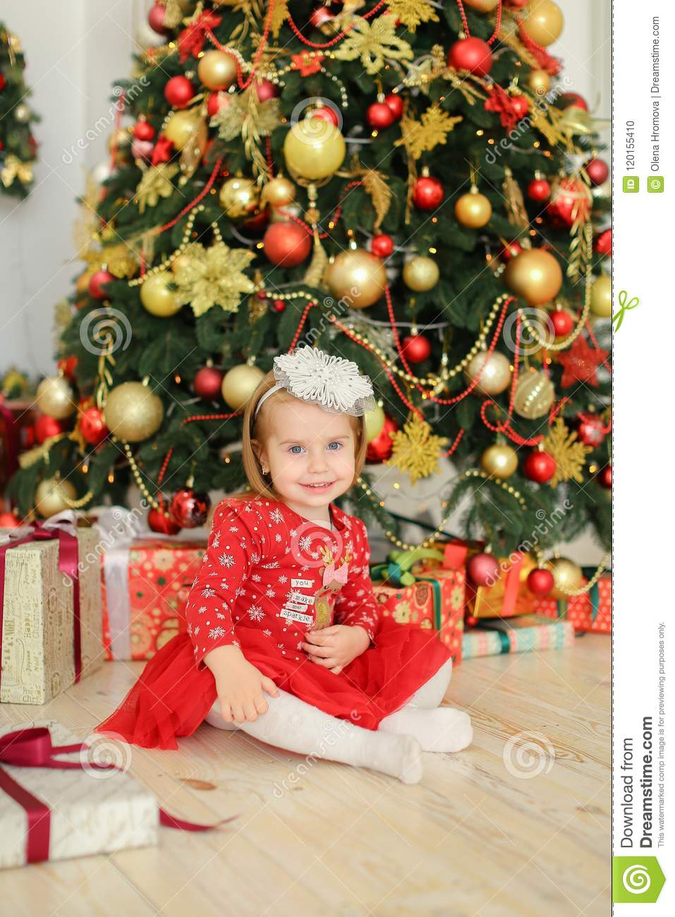 Little Female Kid Wearing Red Dress Sitting On Floor Near Gifts And ...