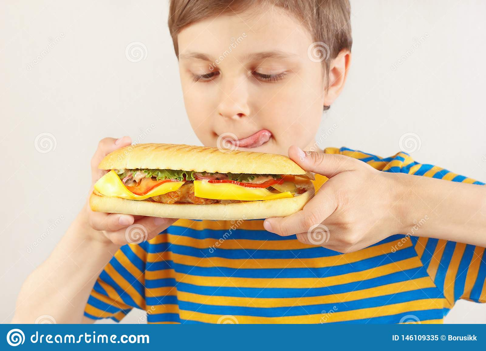 Little funny boy is licked at cheeseburger on white background