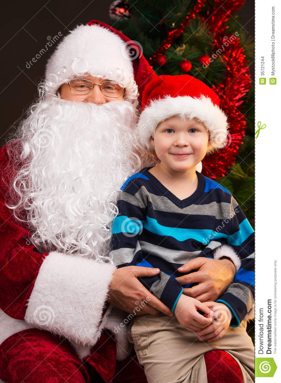 Little Funny Boy Sitting On Santa Claus Laps Stock Images