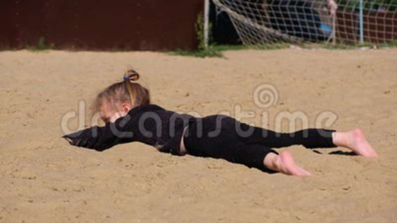 Little funny girl in a black suit swims in the sand imaging the sea or pool. Concept of children`s games and summer expectations stock footage