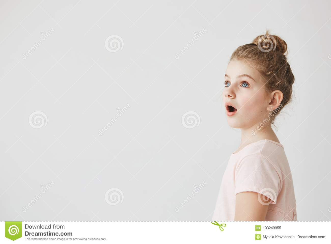 Little Funny Girl With Blonde Hair In Bun Standing With Open Mouth On Street Being