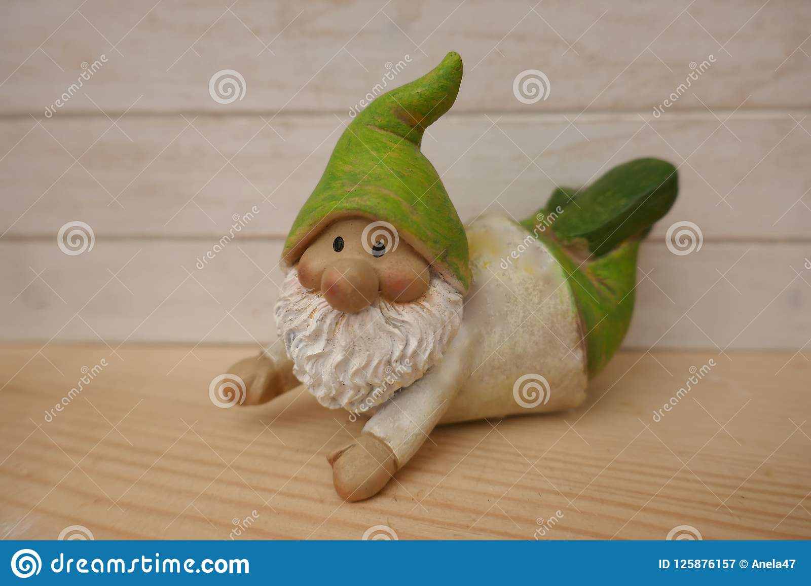 Little Garden Gnome With A Green Hat And White Beard Lies On A ...