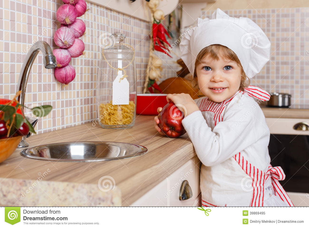 Little Girl In Apron In The Kitchen. Stock Image - Image: 39869495