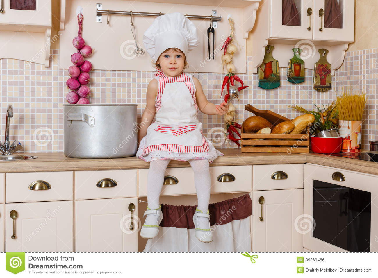 little girl in apron in the kitchen stock photo image 39869486
