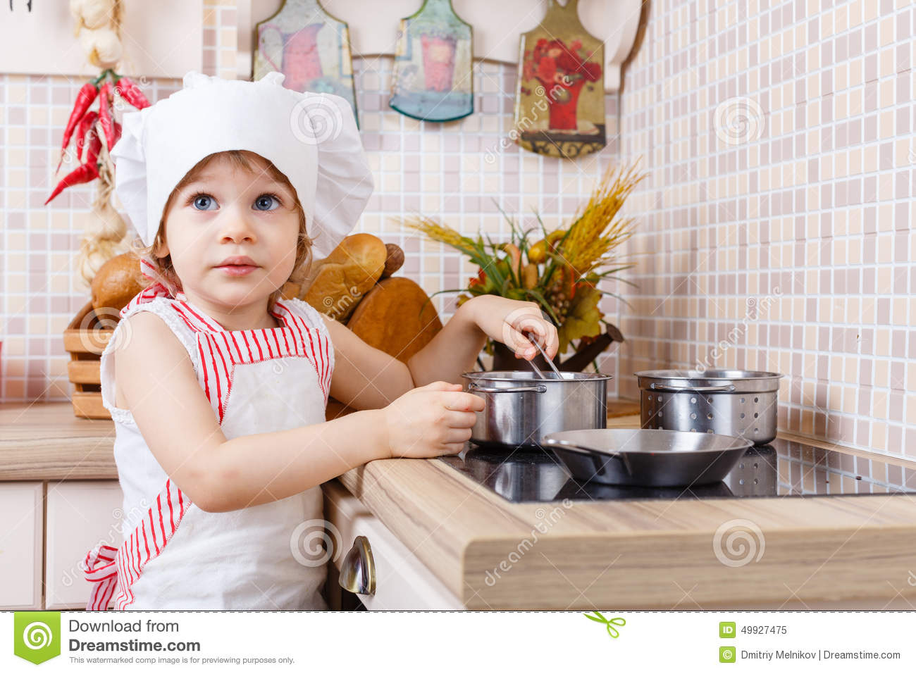little girl in apron in the kitchen stock photo image 49927475