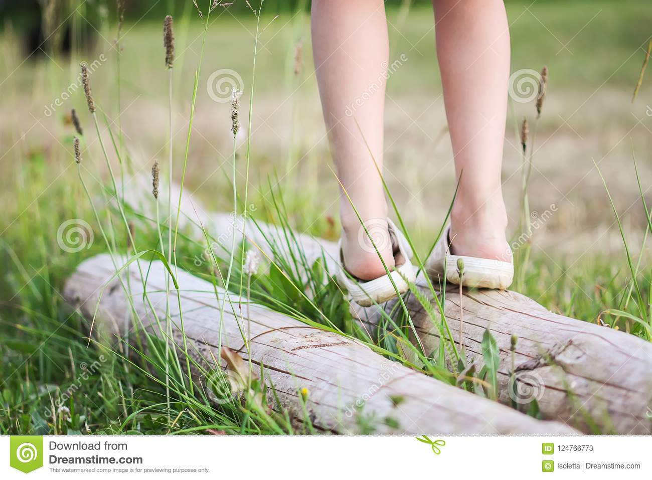 Little girl balancing on a log in summer park. Child& x27;s legs and green grass close up.