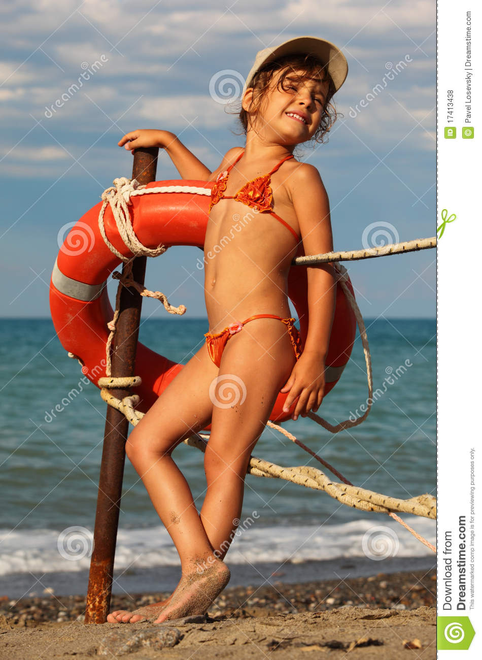 Beautiful little girl in bathing suit and cap standing on beach. she ...