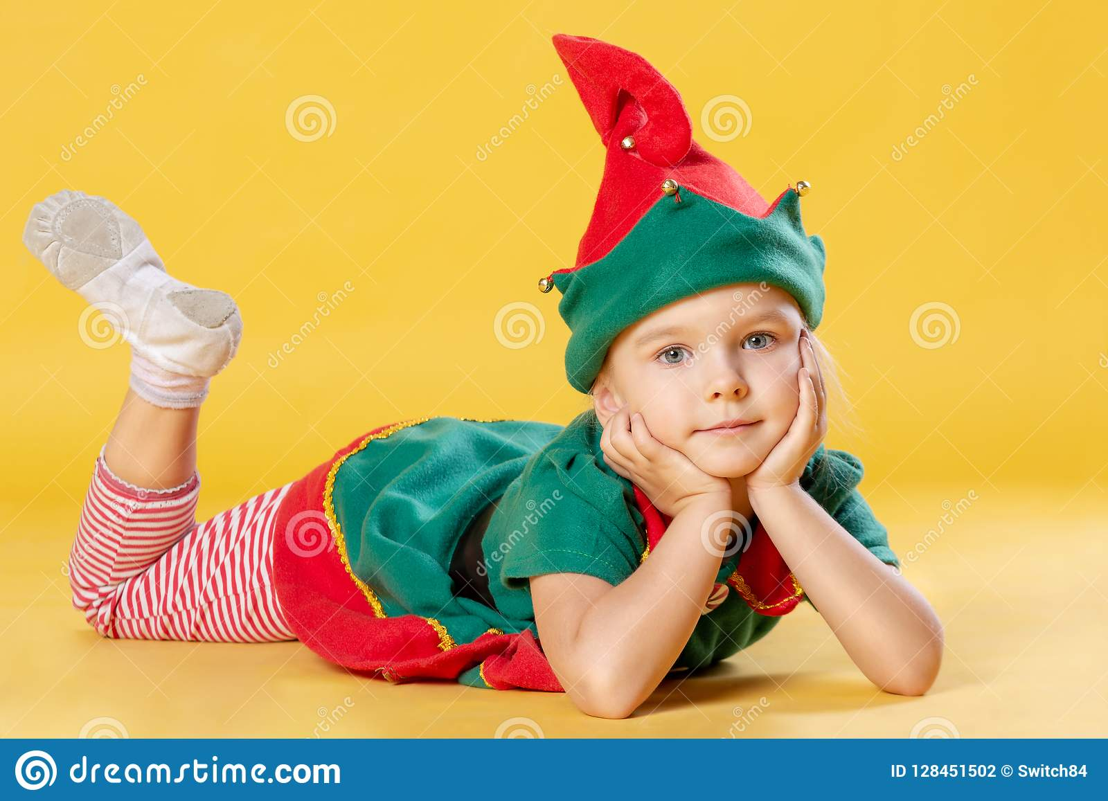 Little Girl With Blond Hair In A Christmas Elf Costume The Baby Is Lying On His Stomach Stock Photo Image Of Blonde Gnome 128451502