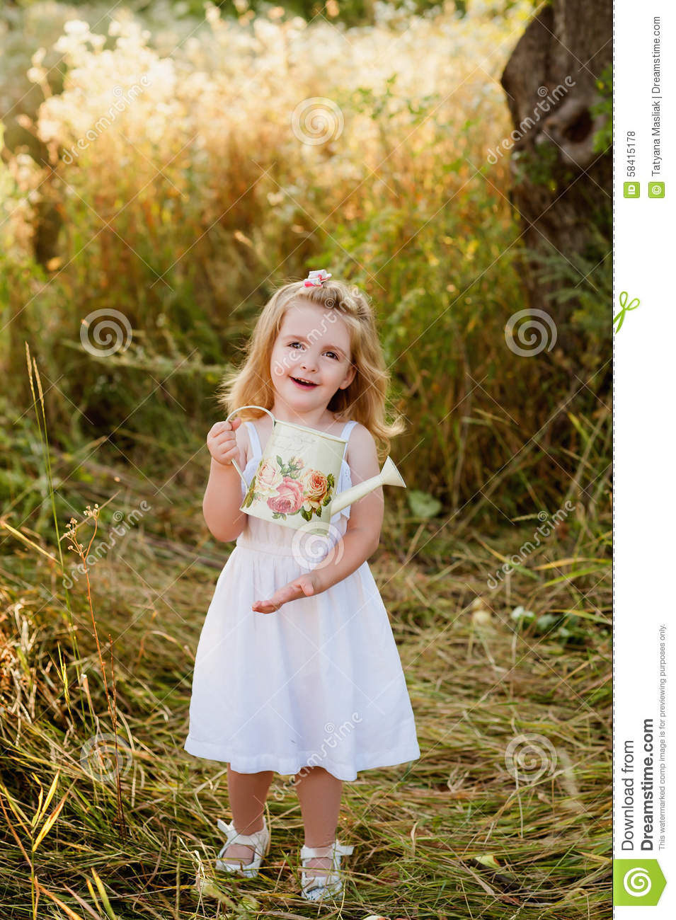Little Girl Blonde In A White Dress In Garden With Watering ...