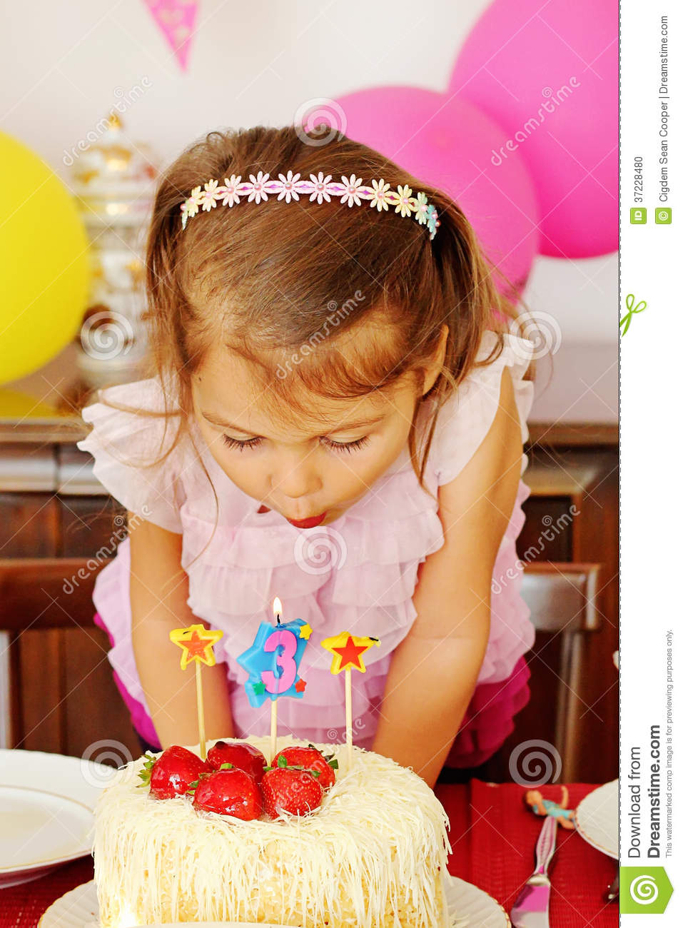 Little girl blowing the candles