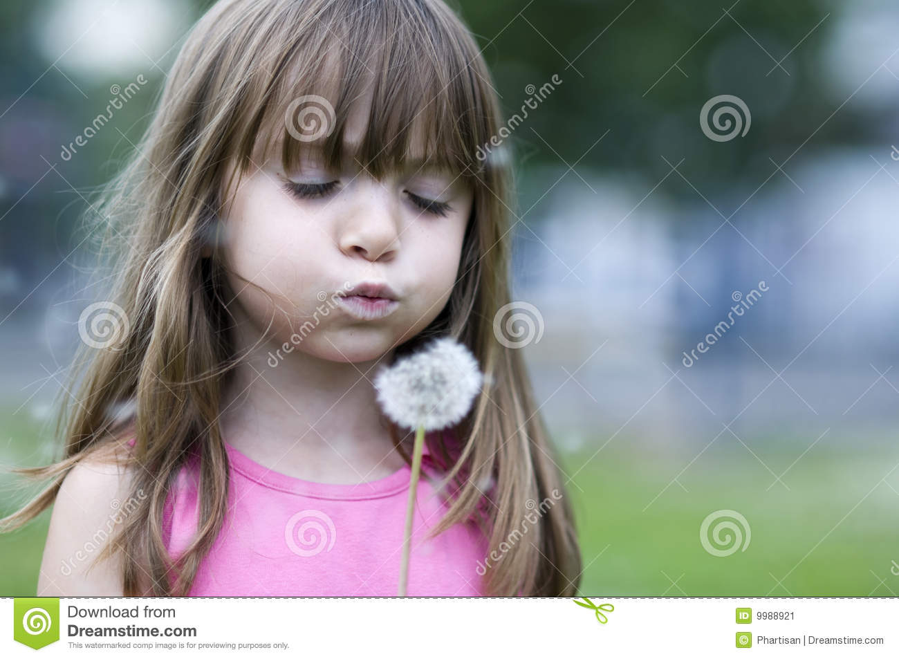 Little girl blowing flower blossom