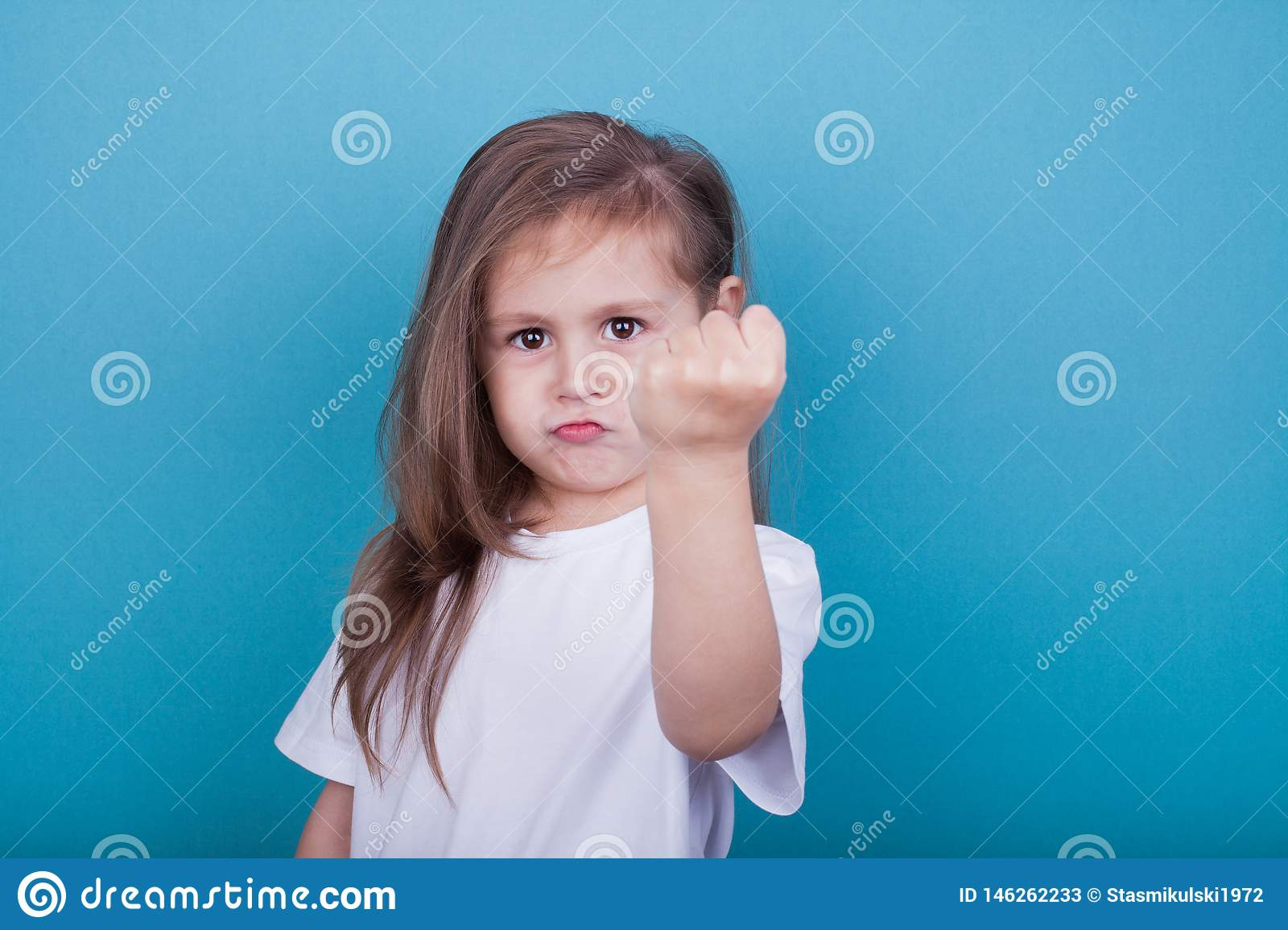 A little girl threatens with a fist