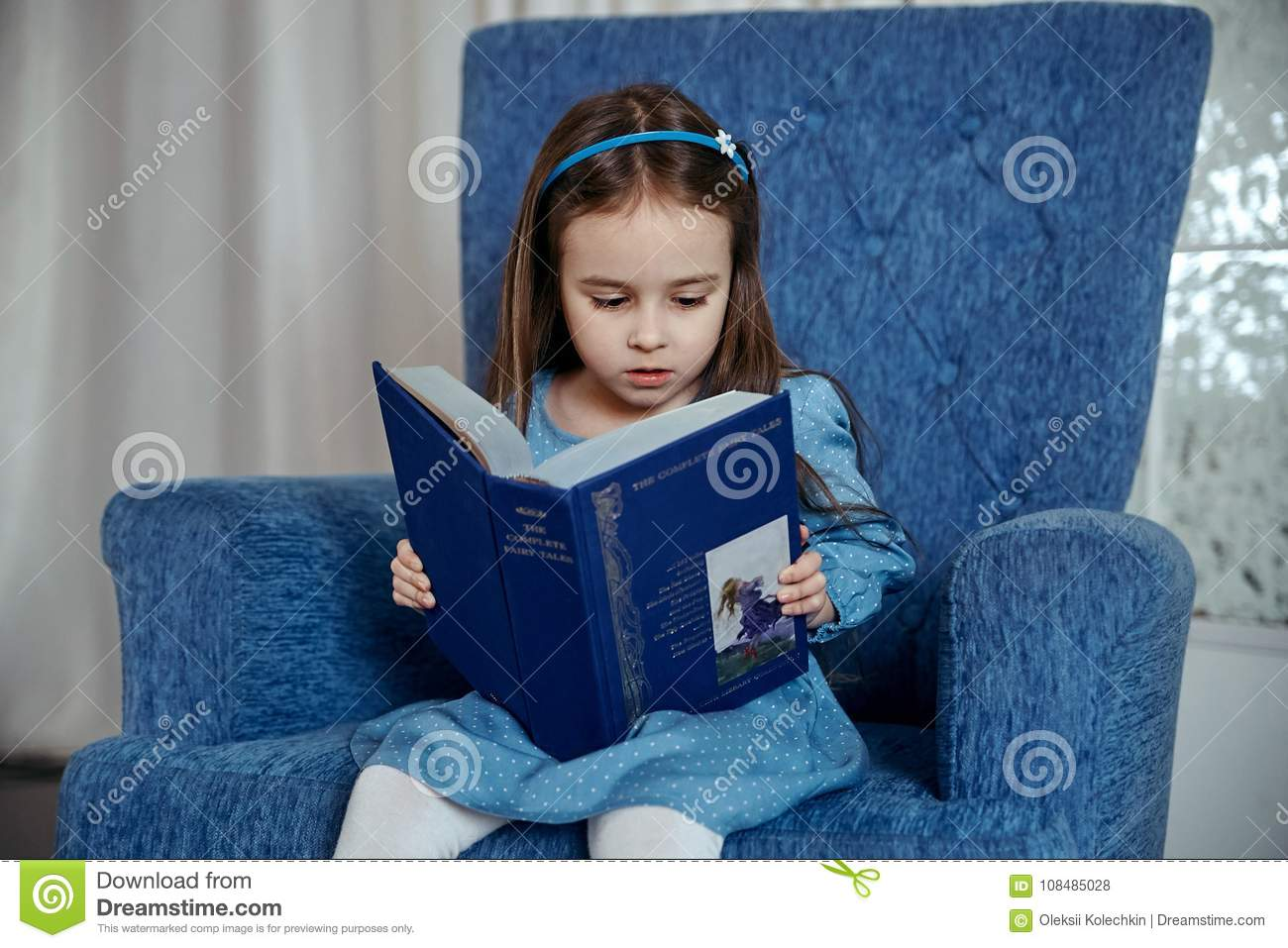little girl in a blue dress is sitting in a blue armchair and is