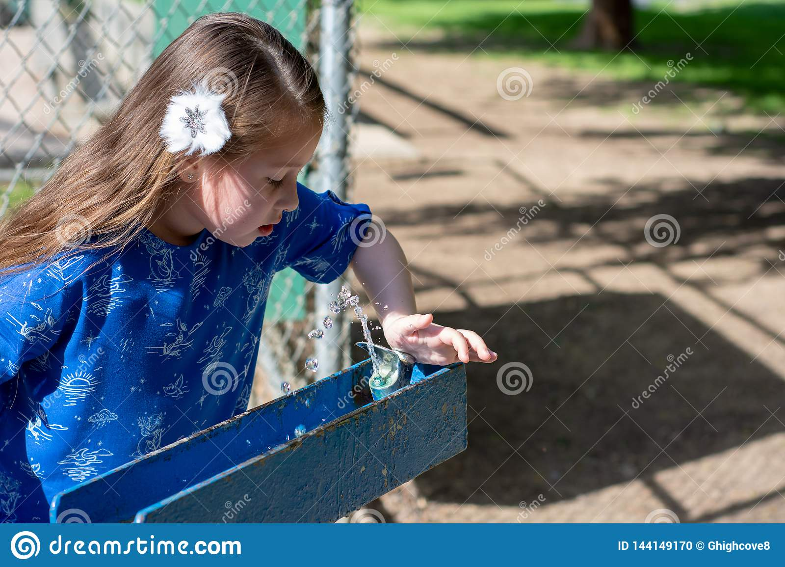 Little Girl in Blue Dress Using Drinking Fountain