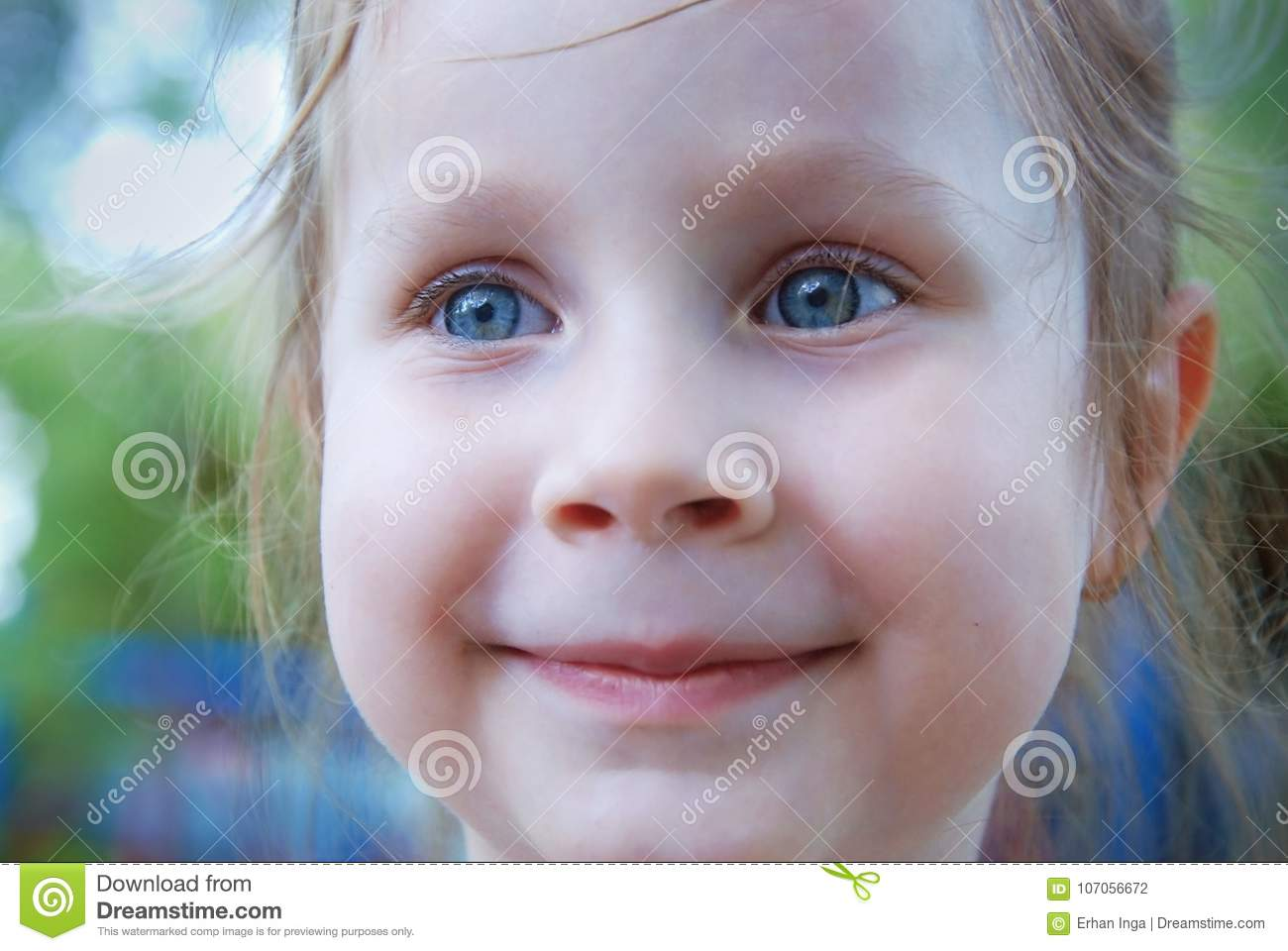 Little Girl with Blue Eyes Smiling over Blured Summer Background.
