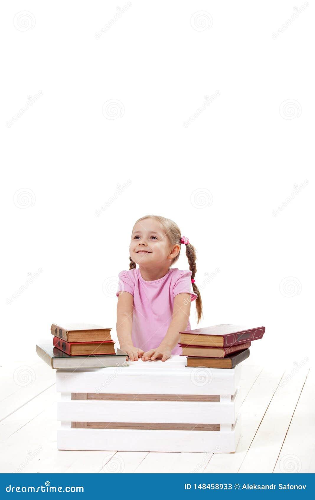 Joyful little girl with books sits on a white floor.