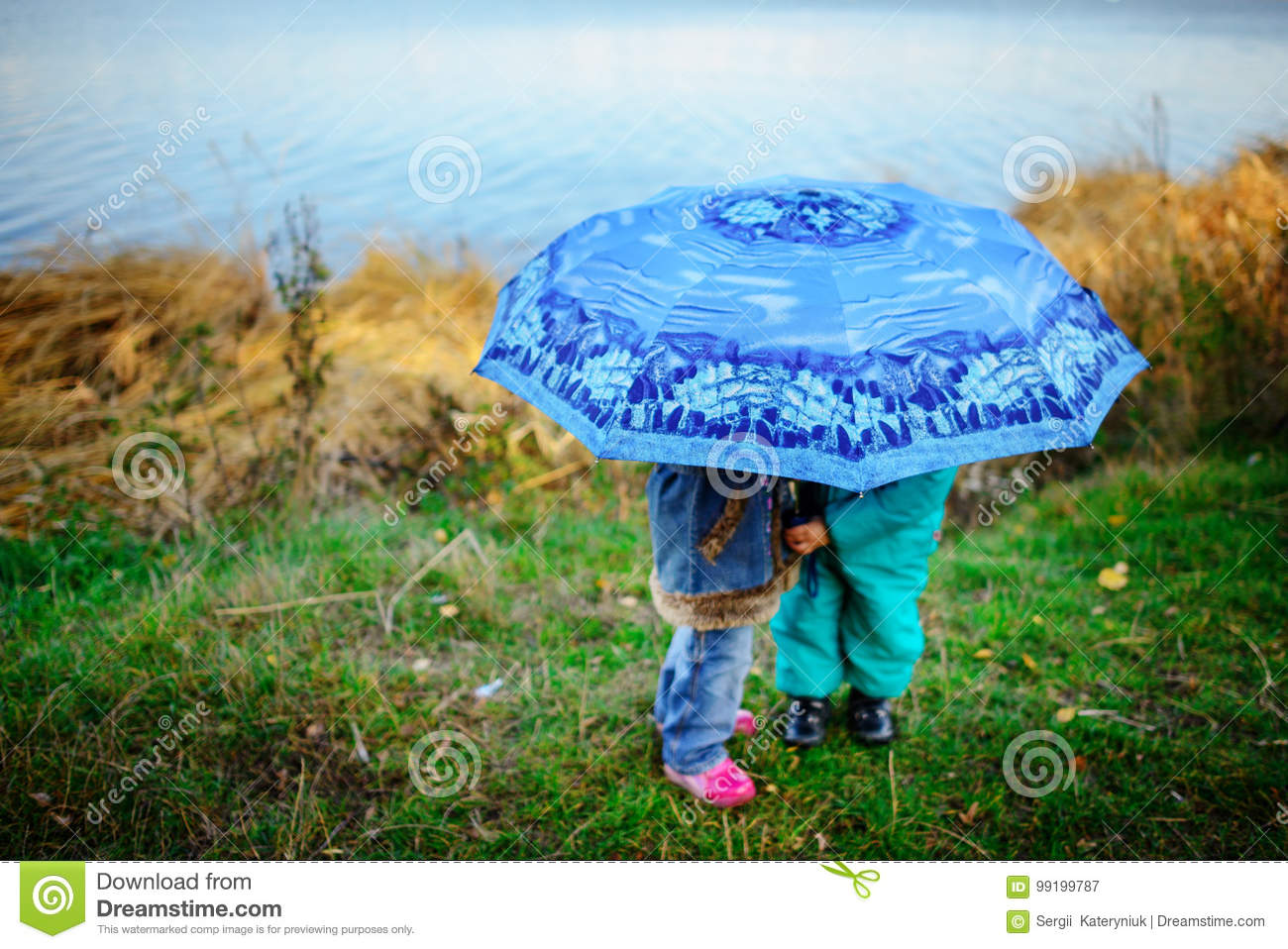 Little Girl And Boy With Umbrella Playing In The Rain