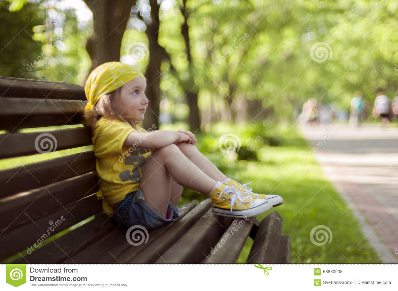 A little girl in a bright yellow bandanna and yellow snaekers sitting on a bench