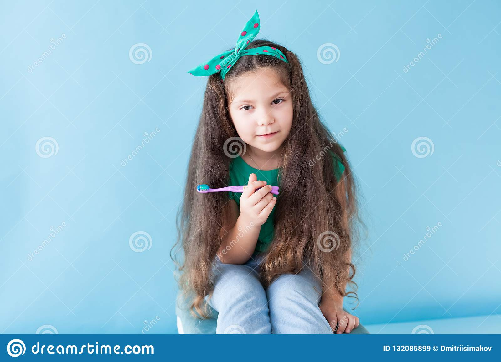 Little girl brushing his teeth with a toothbrush dent