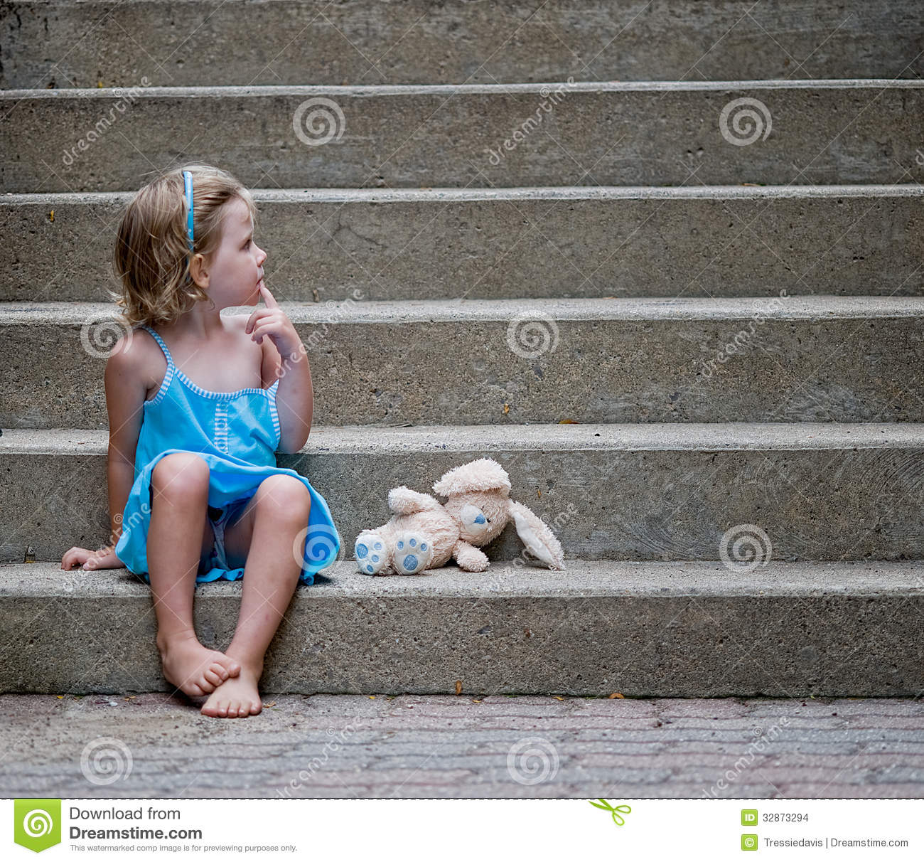 Cute little girl wearing blue dress sitting on concrete steps with her ...