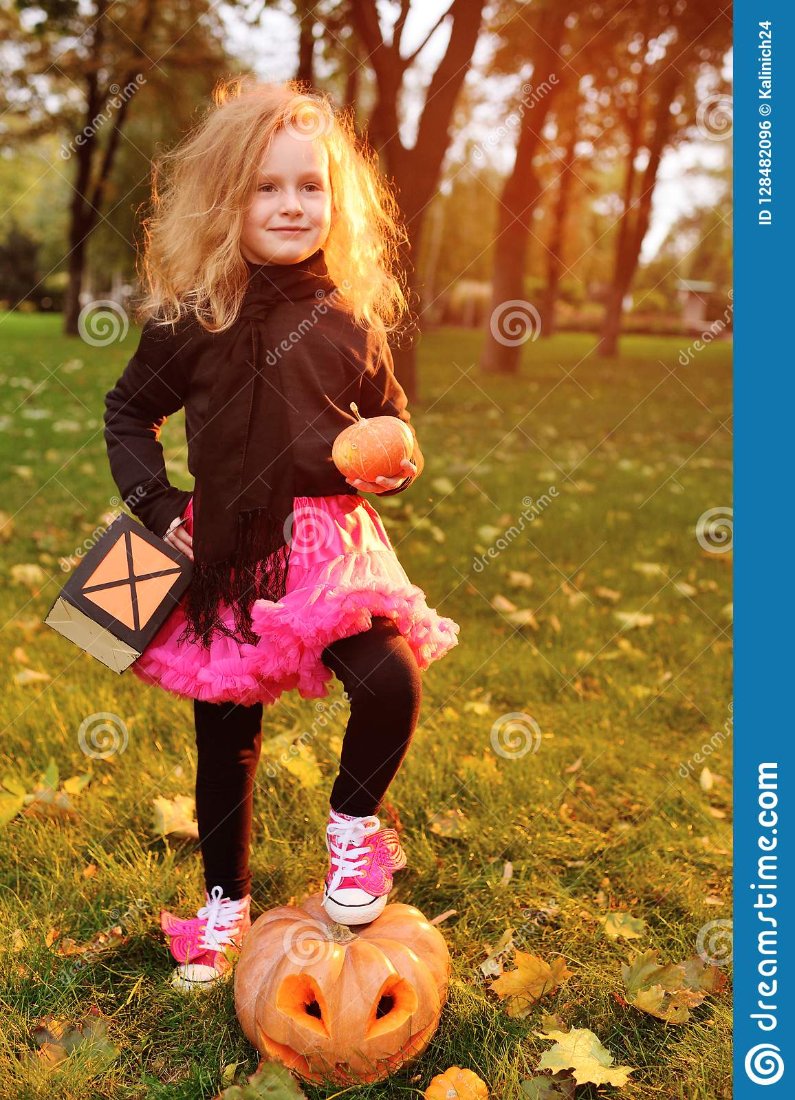 d24f663db475 Baby little girl in carnival costume with pumpkin celebrating halloween