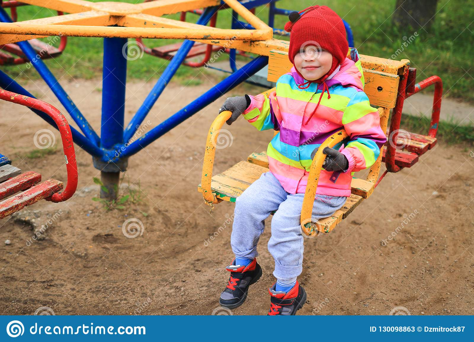 5c178c7f8 Little girl child on the carousel in the playground. The child is riding on  a