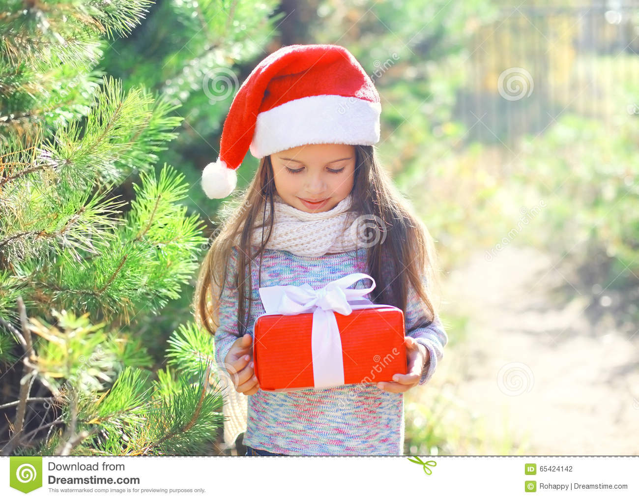 Little girl child in christmas santa hat with gift box stock photo