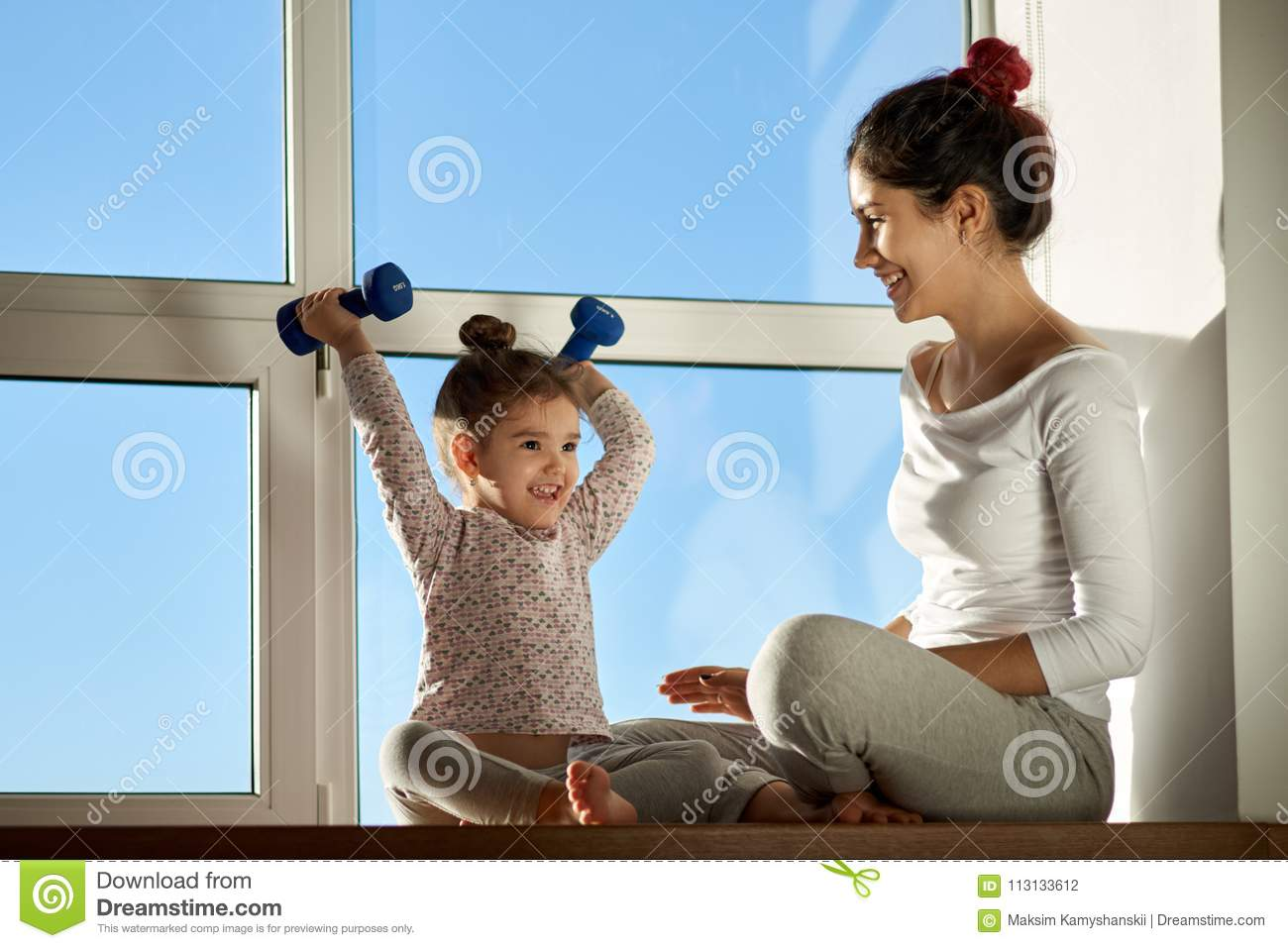 Little girl child happily raises on a dumbbell and smiles, showing off his achievements to his mother.