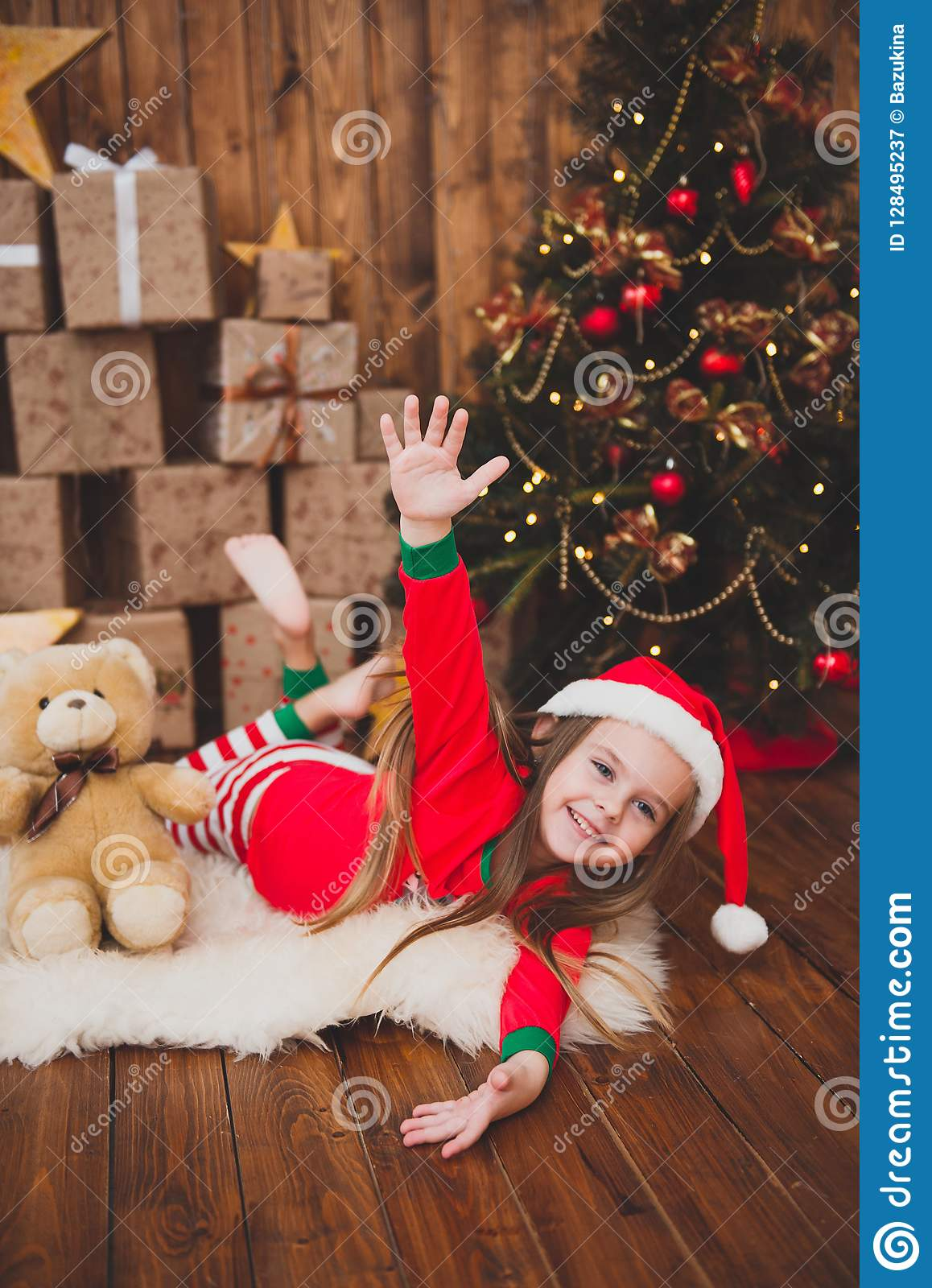 Little Girl In Christmas Pajamas And Santa Hat In ...