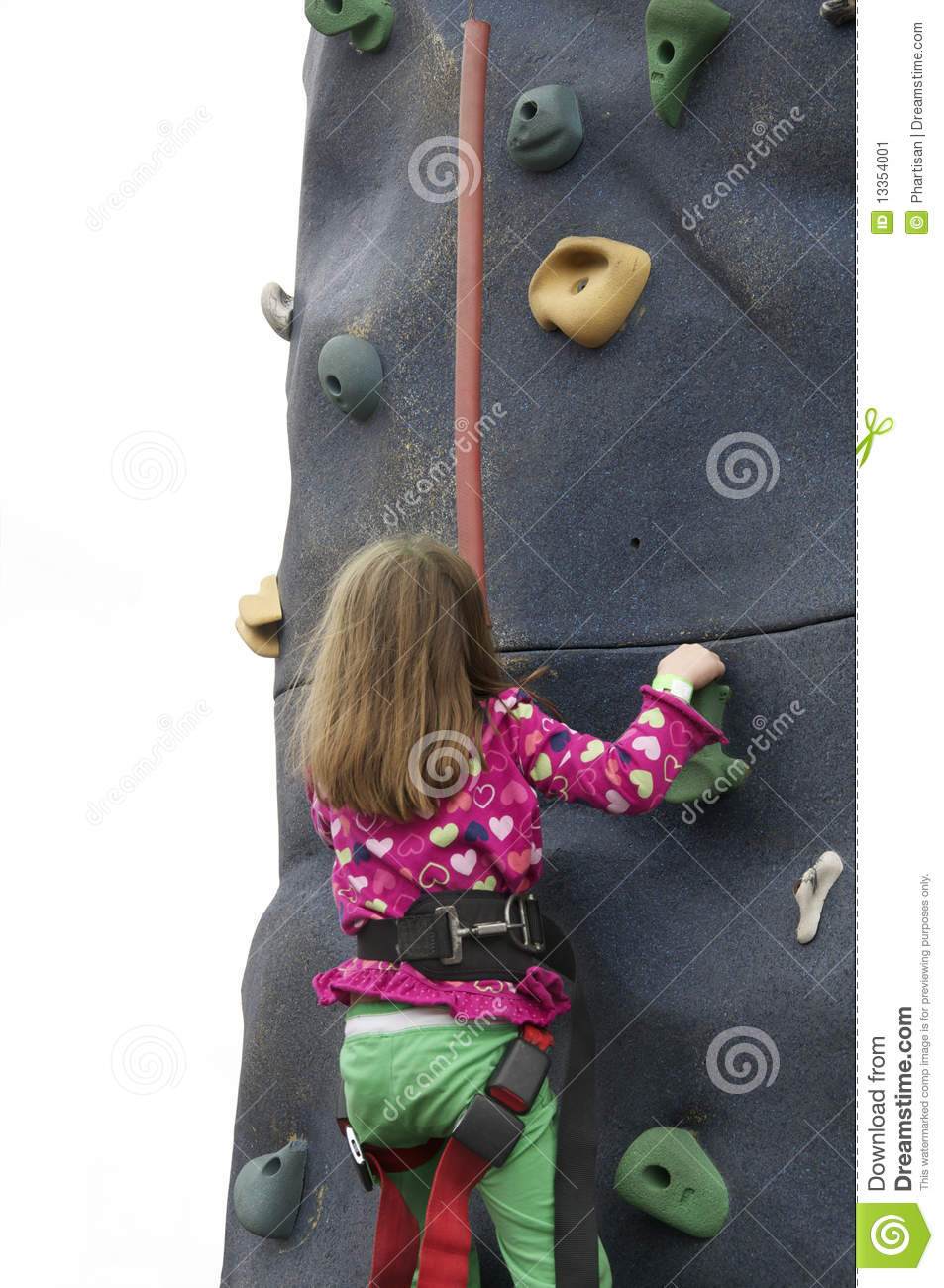 Little girl climbing rock wall at festival event