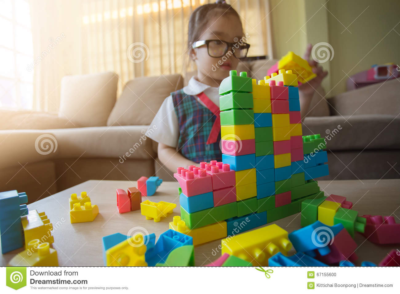 Little girl in a colorful shirt playing with construction toy blocks building a tower
