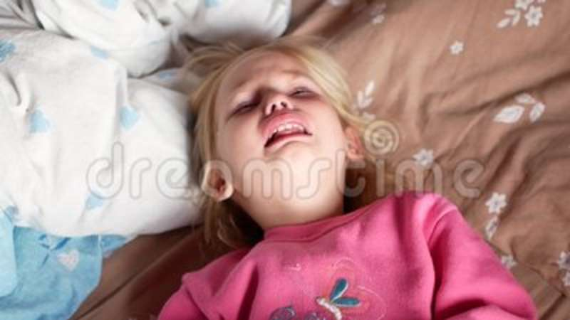 A little girl is crying on the bed  The child is very upset, he has  hysterics  Baby, innocence