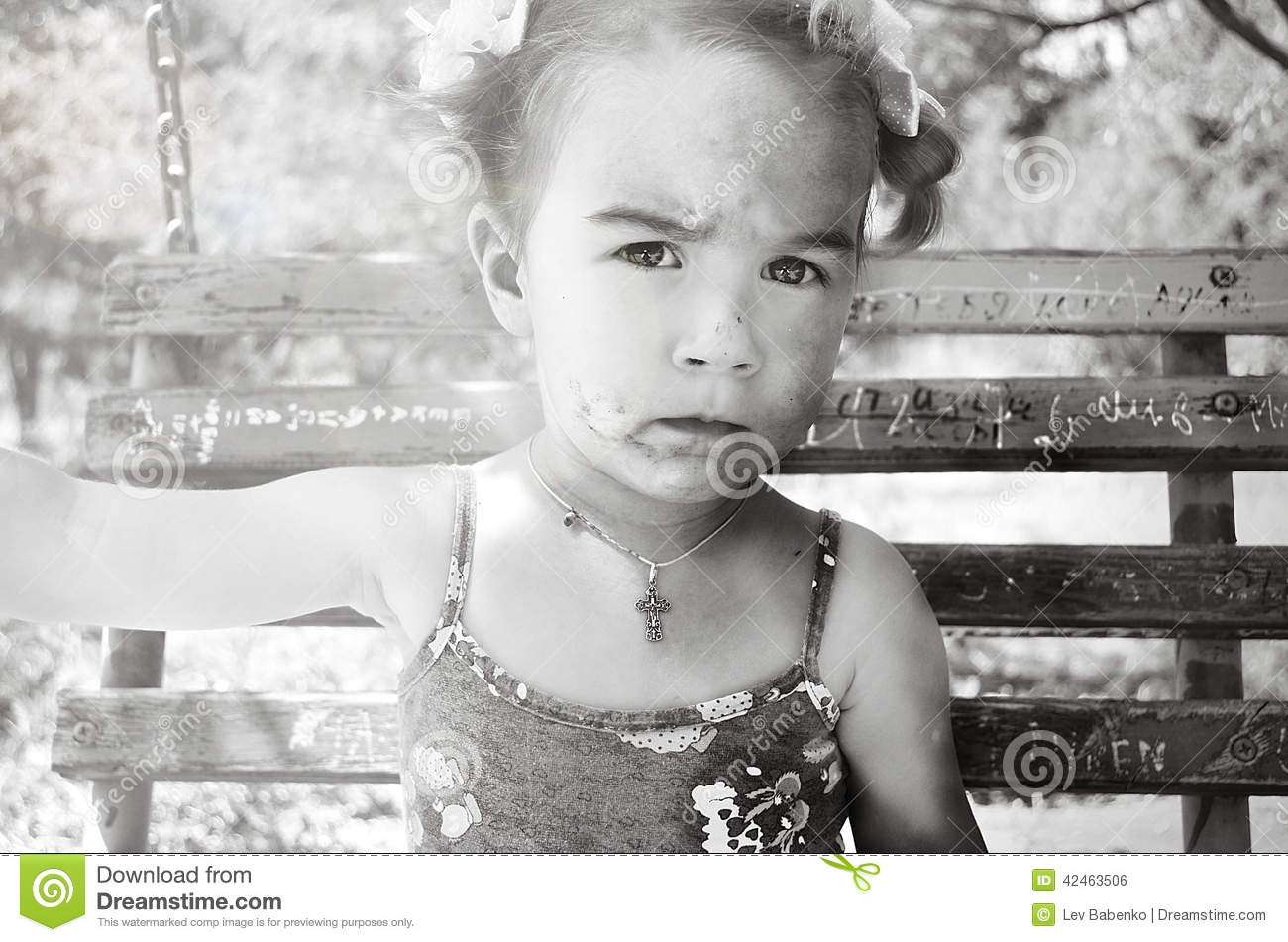 Little girl with a dirty face and bows on a swing
