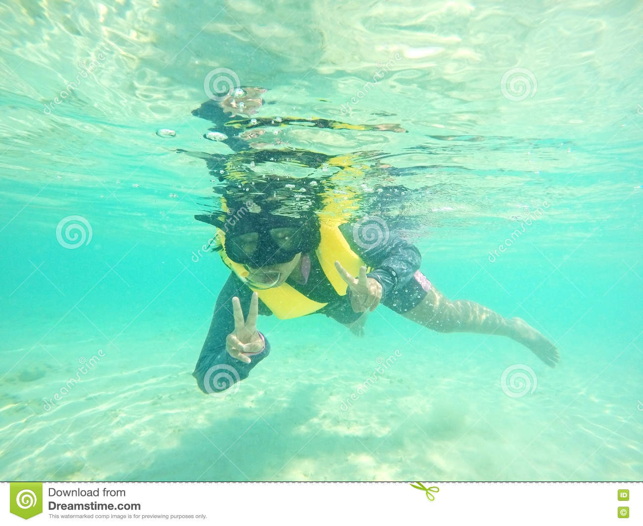 Little girl dive underwater with deep blue sea.