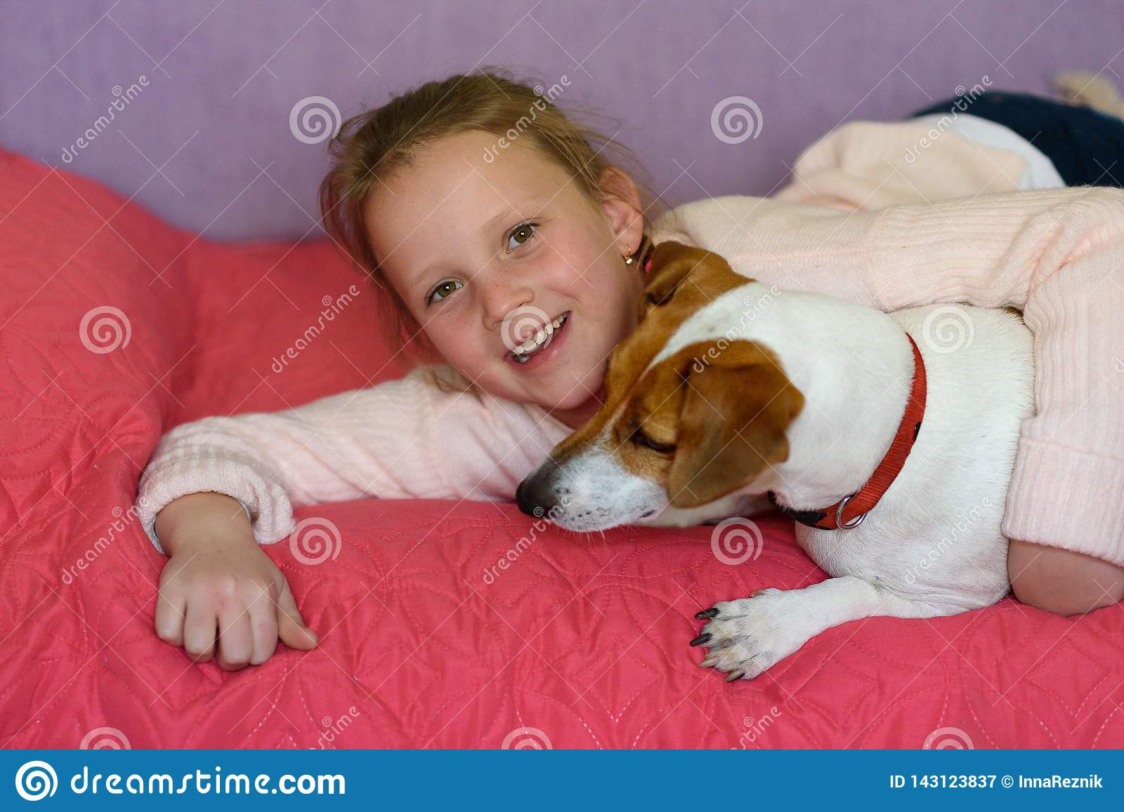 Little girl with dog at home in playroom.