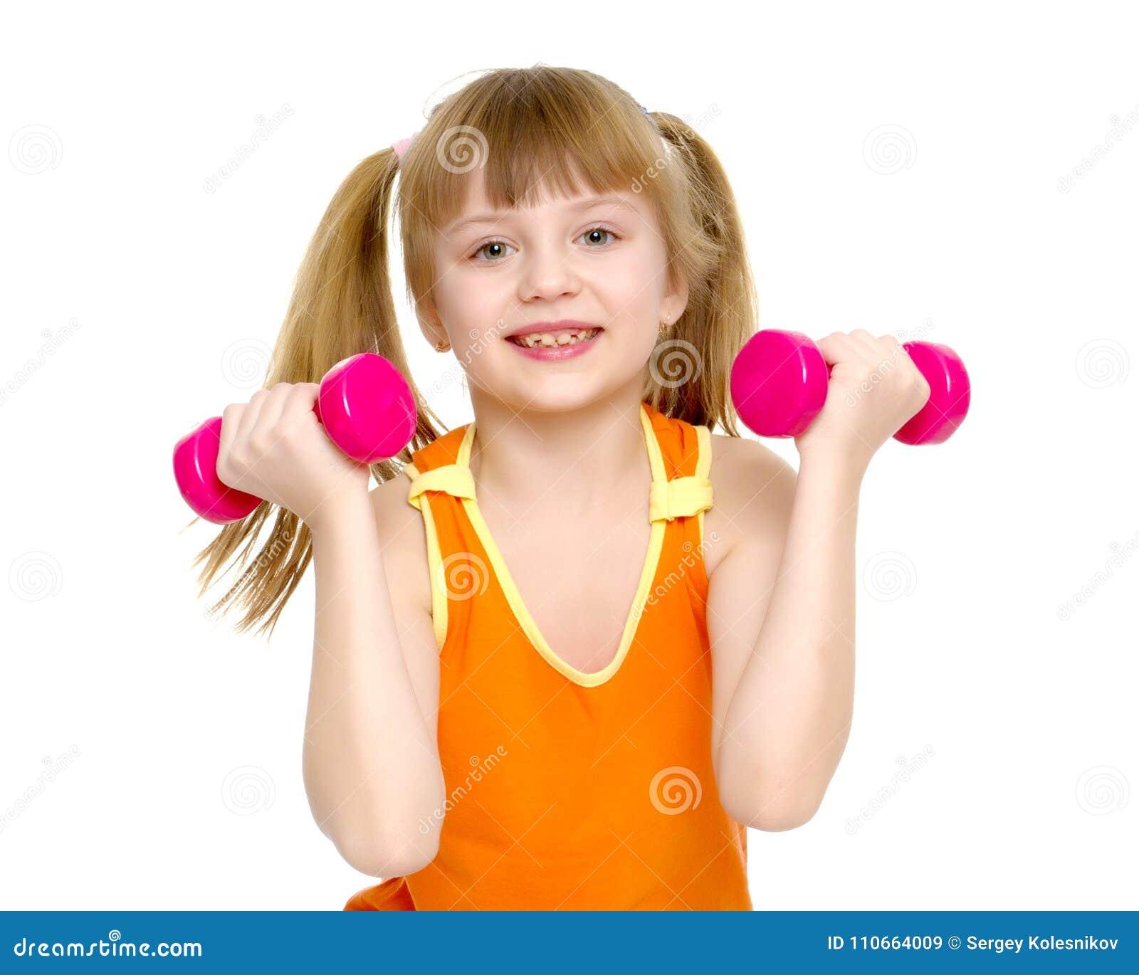 Little girl doing exercises with dumbbells.