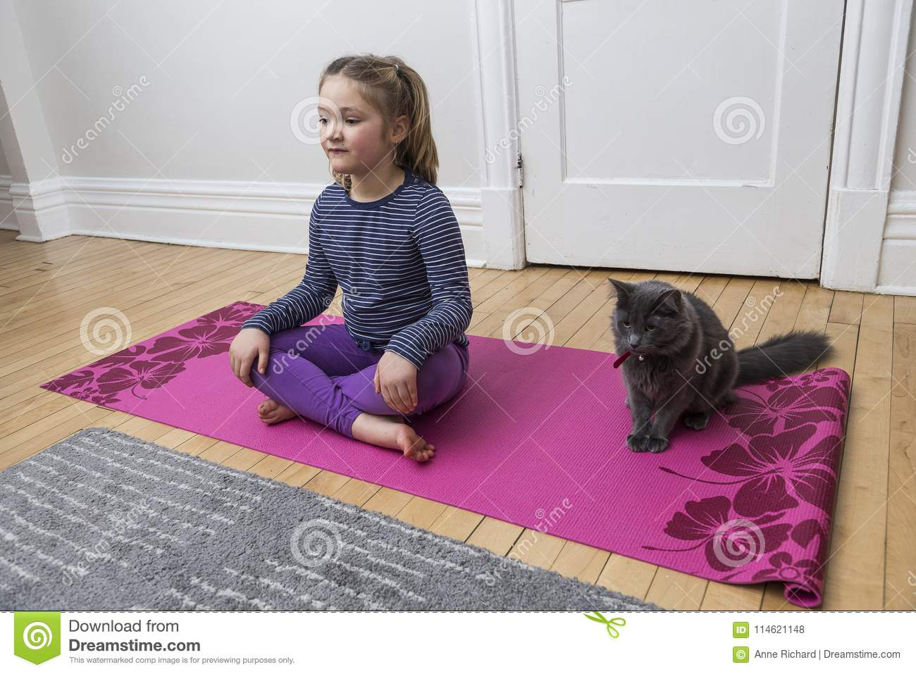 Little girl doing the yoga crossed-legged sitting pose with grey cat