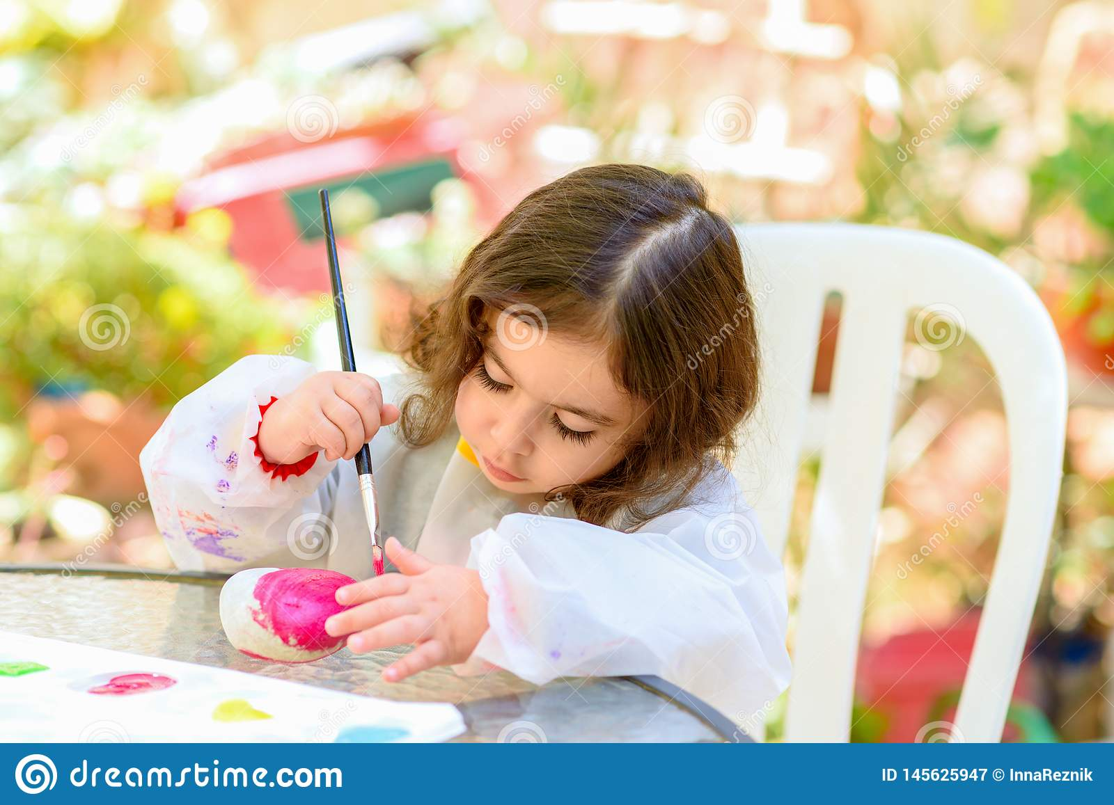 Little Girl Drawing On Stone Outdoors In Summer Sunny Day.