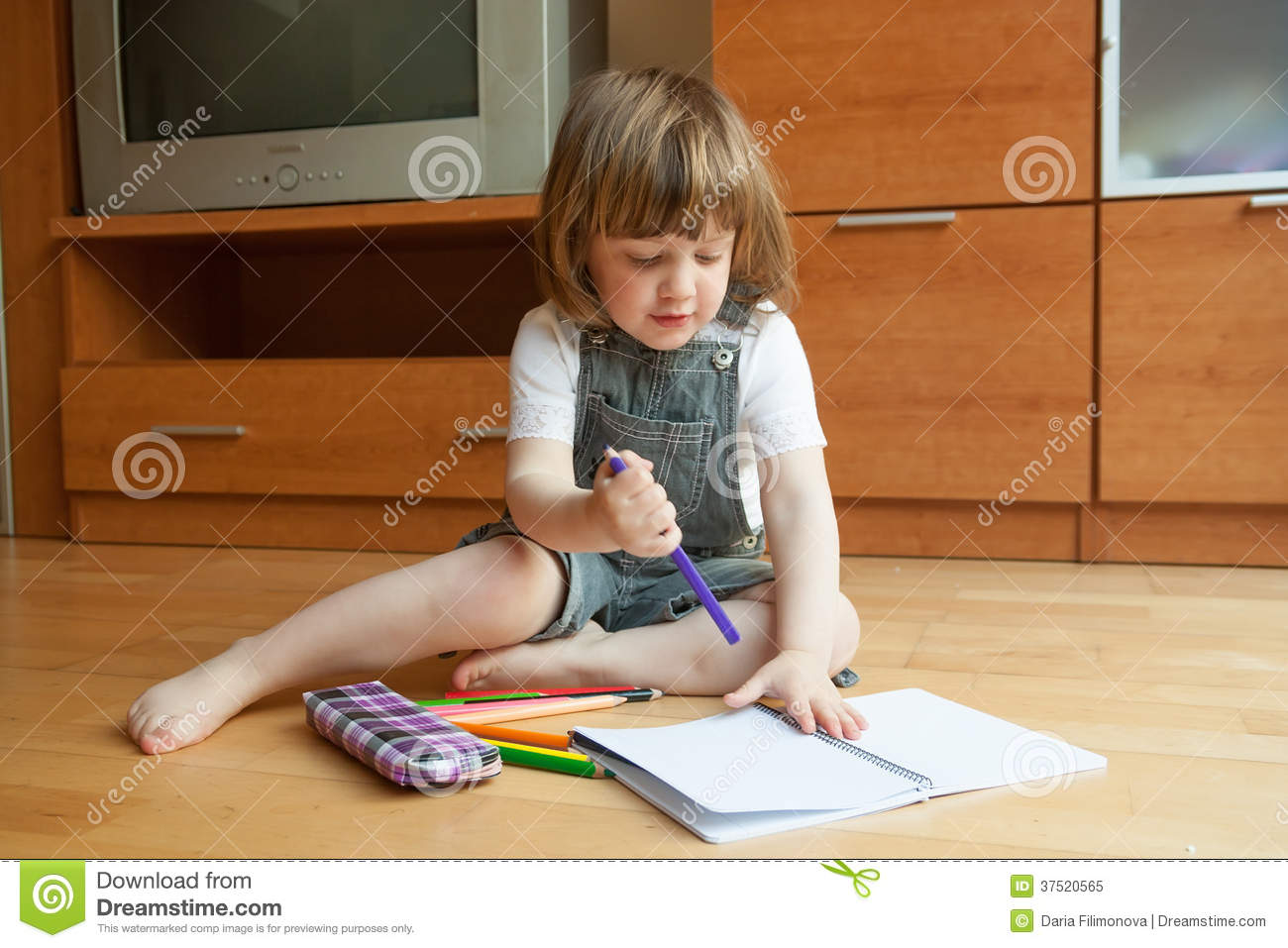 Little girl draws while sitting