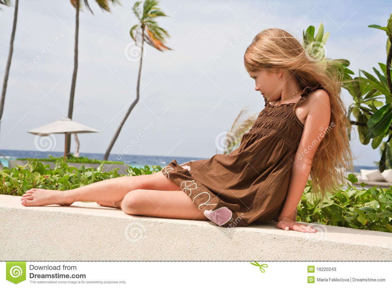 Thoughtful girl sitting near ocean in a dream.