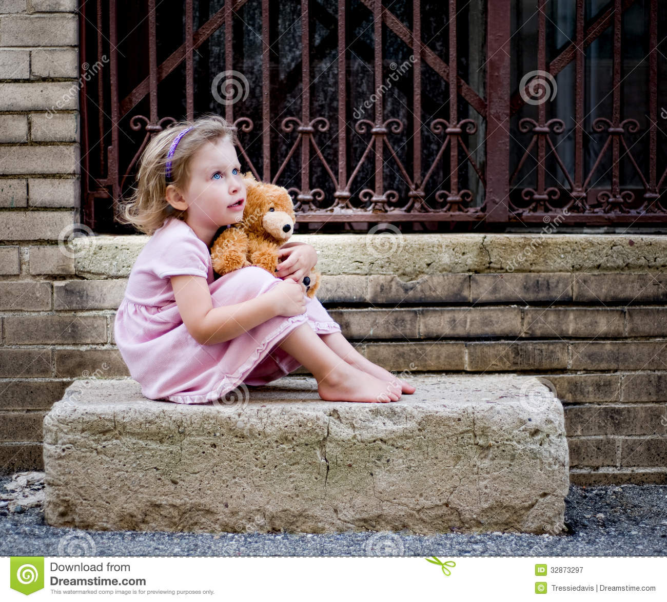 474e371b58 Happy little girl wearing pink dress sitting on concrete step holding teddy  bear and looking up