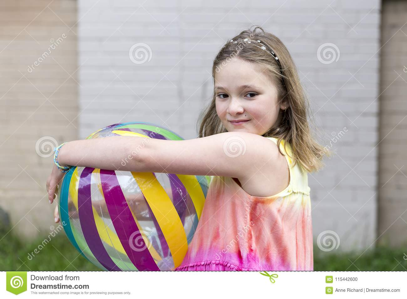 Little girl with dreamy look holding multicolored beach ball