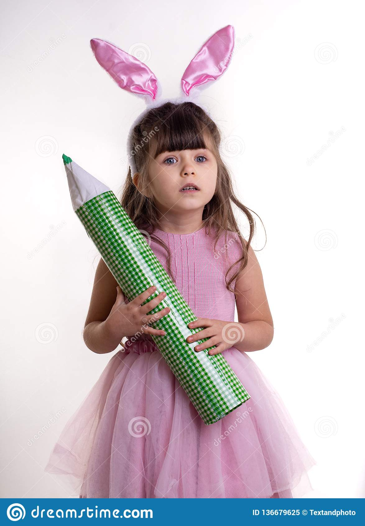 Little girl dressed as the Easter bunny standing on white background and holding pencil