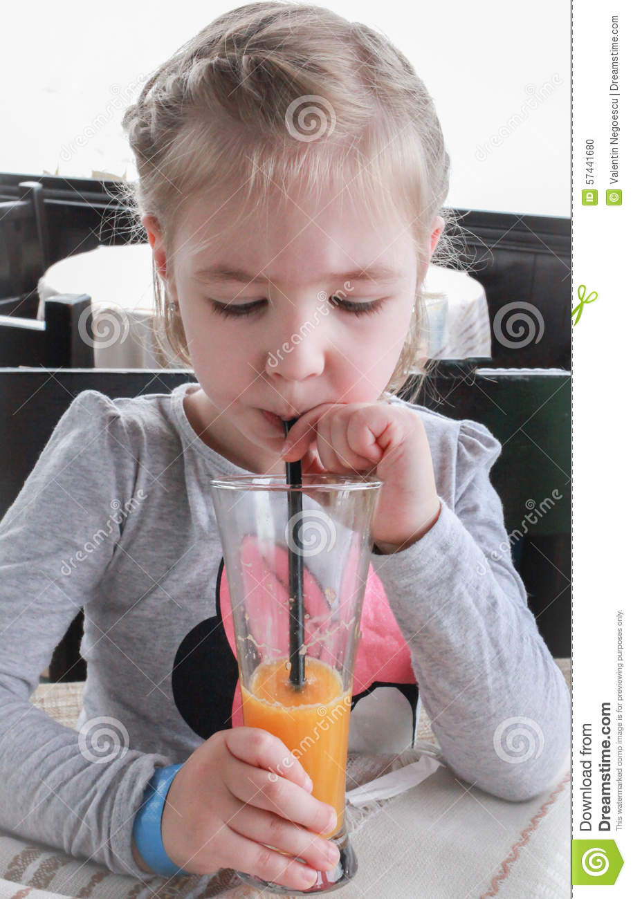 little girl drink juice through a straw stock photo