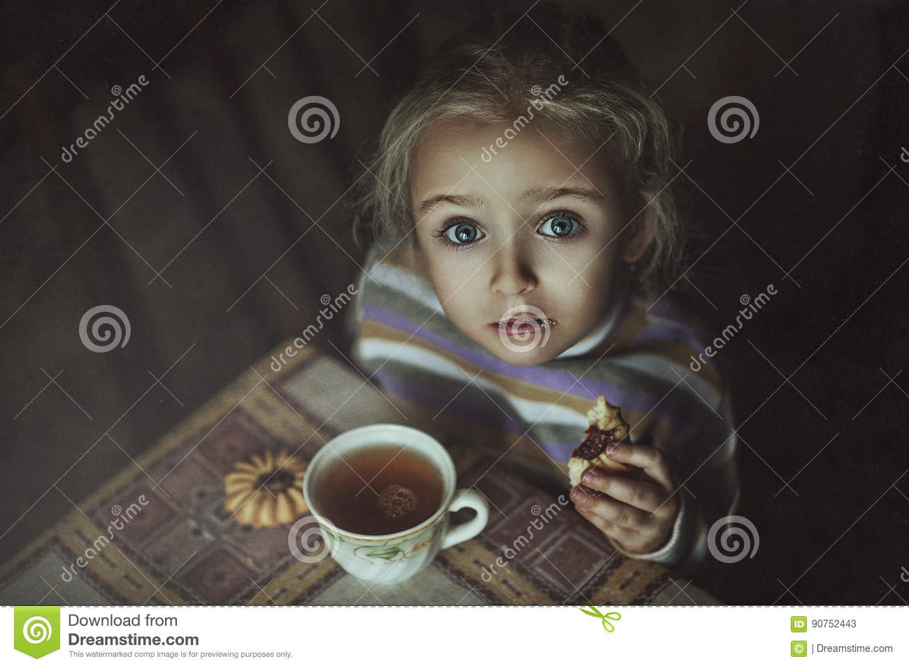 Little girl drinking tea with biscuits