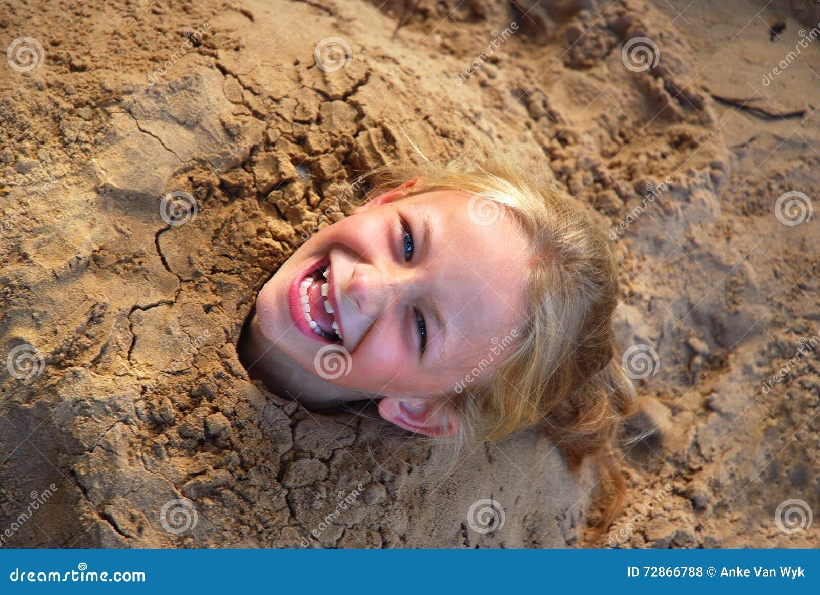 Little girl dug into sand